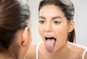 woman looking at tongue with dry mouth